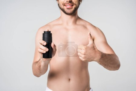 partial view of smiling man with male deodorant showing thumb up isolated on grey