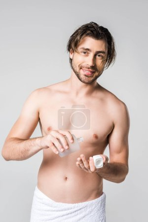 portrait of smiling man in white towel with male perfume isolated on grey
