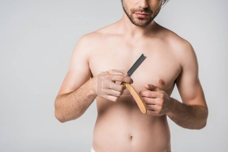 partial view of shirtless man with straight razor in hands isolated on grey