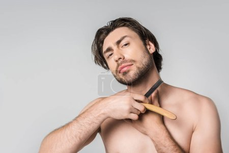 portrait of shirtless man with straight razor in hands isolated on grey