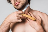 cropped shot of man with straight razor in hands shaving beard isolated on grey