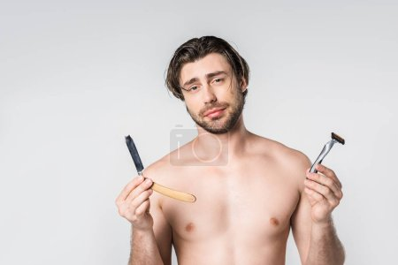 portrait of shirtless man with razors in hands looking at camera isolated on grey