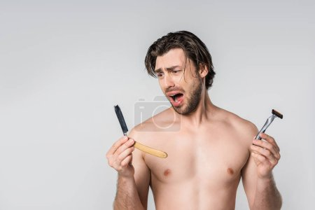 portrait of emotional shirtless man with razors in hands isolated on grey