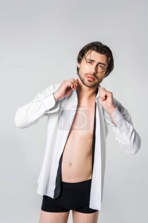 portrait of stylish young man in white shirt and black underwear isolated on grey