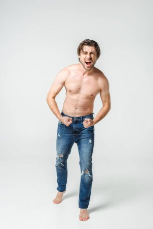 emotional shirtless man in jeans showing muscles on grey backdrop