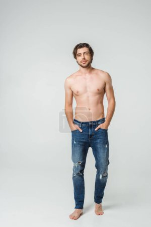 young shirtless man in jeans with hands in pockets posing on grey backdrop