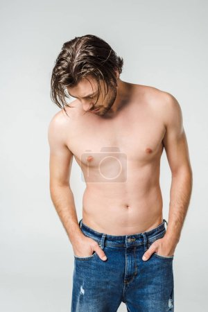 portrait of young shirtless man in jeans isolated on grey