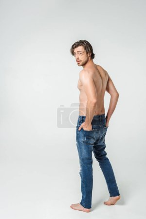 back view of young shirtless man in jeans on grey backdrop