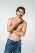 portrait of pensive shirtless man in jeans isolated on grey