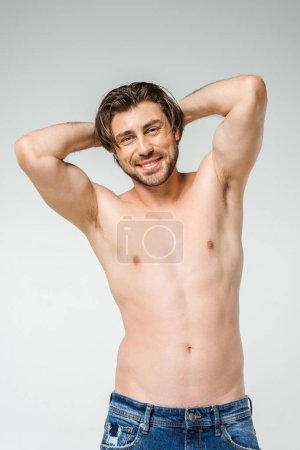 portrait of smiling shirtless man in jeans looking at camera on grey backdrop