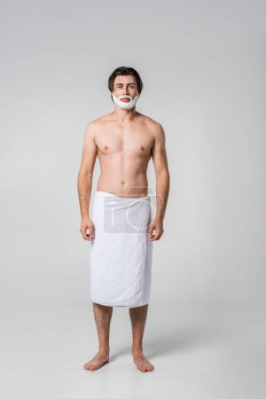 Photo for Shirtless man in towel with shaving foam on face isolated on grey - Royalty Free Image