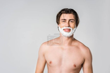 portrait of young man with shaving foam on face looking at camera isolated on grey