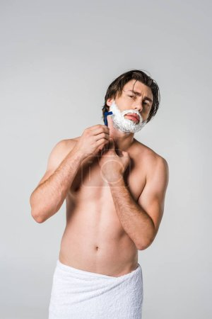 portrait of young man in white towel with shaving foam on face shaving beard isolated on grey