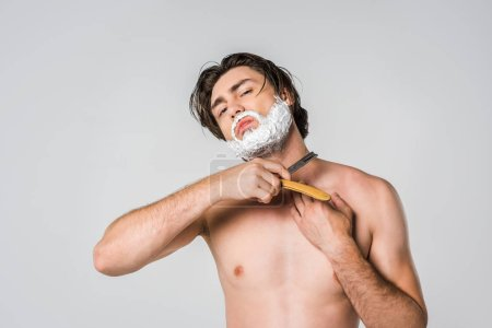 portrait of shirtless man with foam on face shaving beard isolated on grey