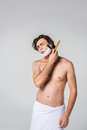 portrait of young man in white towel with shaving foam on face and straight razor isolated on grey