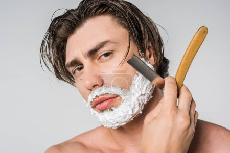 portrait of shirtless man with foam on face shaving beard with straight razor isolated on grey
