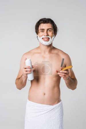 portrait of smiling man in white towel with shaving foam on face and straight razor in hand isolated on grey