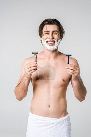 portrait of happy man in white towel with shaving foam on face and razors in hands isolated on grey