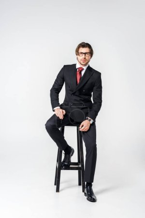 Photo for Young businessman in stylish suit and eyeglasses sitting on chair on grey backdrop - Royalty Free Image