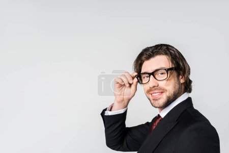 Photo for Side view of smiling businessman in stylish suit and eyeglasses looking at camera isolated on grey - Royalty Free Image
