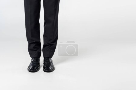 partial view of businessman in stylish clothing on grey background