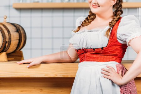 cropped image of oktoberfest waitress in traditional bavarian dress with hand on waist standing near bar counter with beer barrel