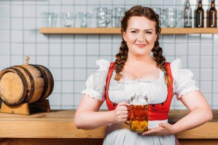 smiling oktoberfest bartender in traditional bavarian dress showing mug of light beer near bar counter