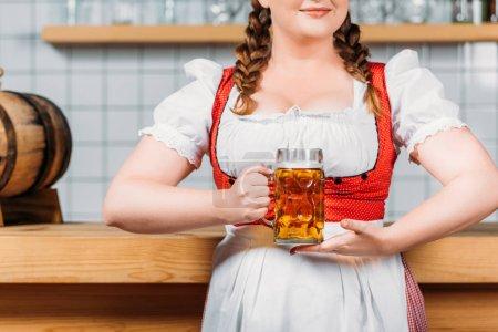 cropped imageo of oktoberfest bartender in traditional bavarian dress holding mug of light beer near bar counter