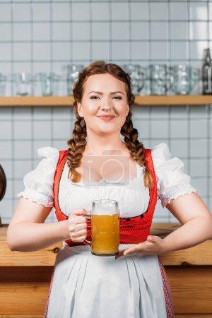 smiling oktoberfest waitress in traditional bavarian dress showing mug of light beer near bar counter