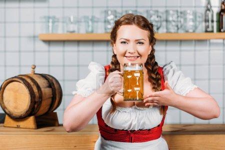 happy oktoberfest waitress in traditional bavarian dress smelling light beer near bar counter