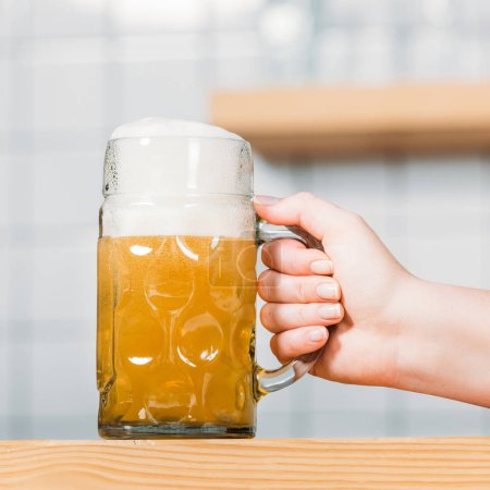 cropped image of female bartender putting mug of light beer with foam on bar counter
