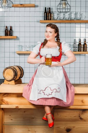 attractive oktoberfest waitress in traditional bavarian dress showing mug of light beer while sitting on bar counter