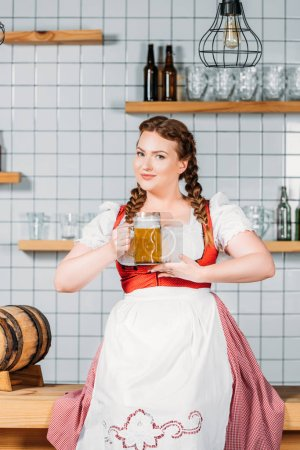 oktoberfest waitress in traditional bavarian dress showing mug of light beer near bar counter