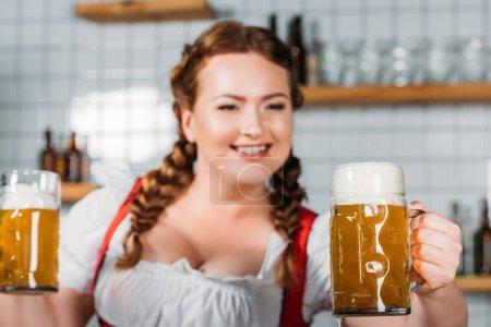 selective focus of oktoberfest waitress in traditional bavarian dress showing mugs of light beer near bar counter