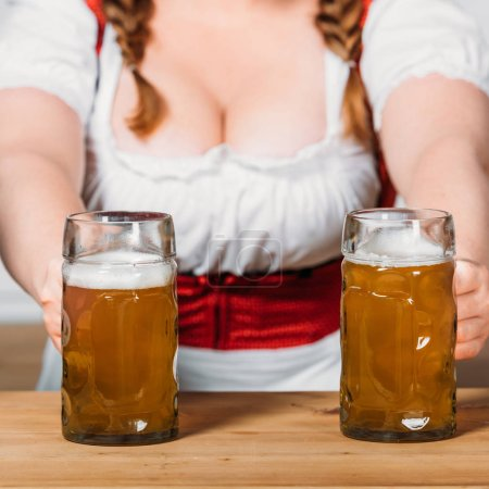 partial view of oktoberfest waitress in traditional bavarian dress putting mugs of light beer on bar counter