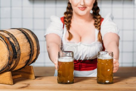 oktoberfest waitress in traditional bavarian dress putting mugs of light beer on bar counter with beer barrel