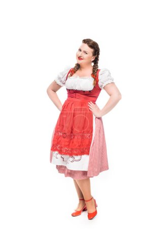 smiling oktoberfest waitress in traditional bavarian dress with hands on waist isolated on white background