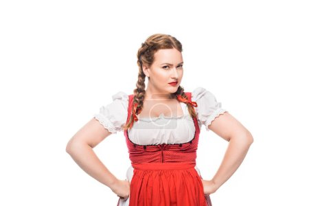 confident oktoberfest waitress in traditional bavarian dress standing with hands on waist isolated on white background