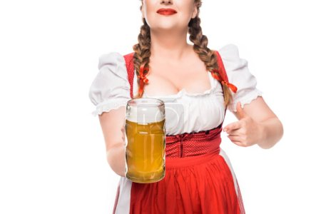 cropped image of oktoberfest waitress in traditional bavarian dress pointing by finger at mug of light beer isolated on white background