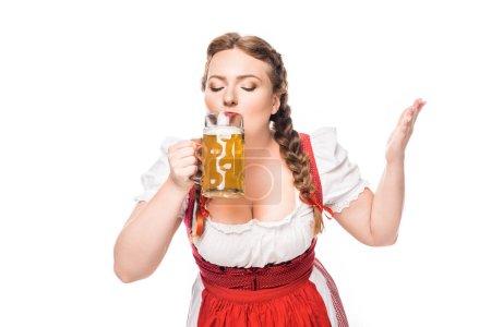 oktoberfest waitress in traditional bavarian dress drinking light beer isolated on white background