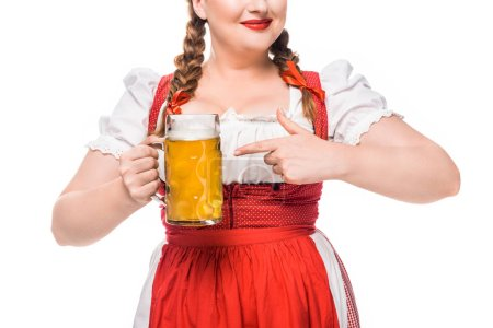 partial view of oktoberfest waitress in traditional bavarian dress pointing by finger on mug of light beer isolated on white background
