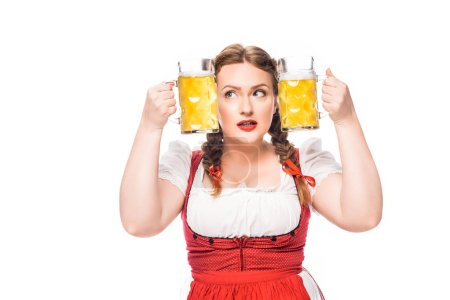 oktoberfest waitress in traditional bavarian dress putting head between mugs of light beer isolated on white background
