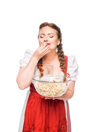happy oktoberfest waitress with closed eyes in traditional bavarian dress eating popcorn from bowl isolated on white background