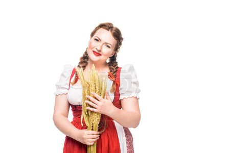 smiling oktoberfest waitress in traditional bavarian dress holding wheat ears isolated on white background