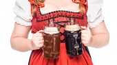 cropped image of oktoberfest waitress in traditional bavarian dress holding mugs with light and dark beer isolated on white background
