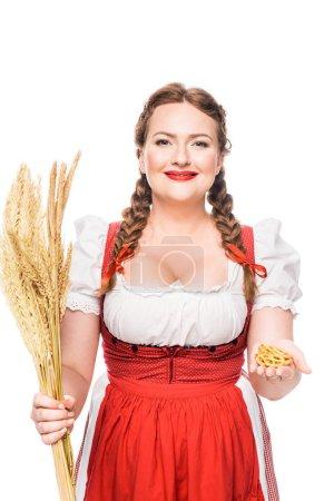 Photo pour Serveuse oktoberfest en tenue bavaroise traditionnelle montrant de petits bretzels et tenant des épis de blé isolés sur fond blanc - image libre de droit