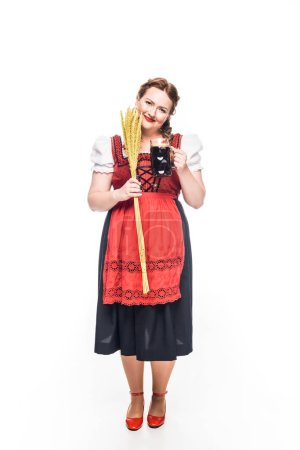 happy oktoberfest waitress in traditional german dress holding wheat and mug of brown beer isolated on white background