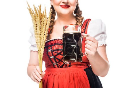 cropped image of oktoberfest waitress in traditional bavarian dress holding mug of dark beer and wheat isolated on white background