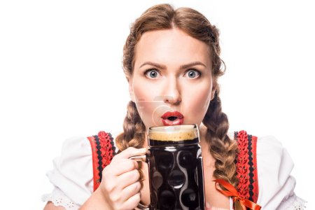 shocked oktoberfest waitress in traditional bavarian dress holding mug of dark beer isolated on white background