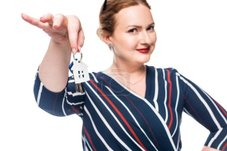 selective focus of female realtor showing keys from house isolated on white background
